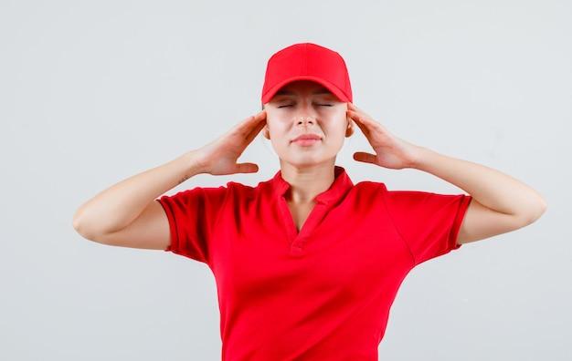 Kobieta dostawy w czerwonej koszulce i czapce, trzymając się za ręce do głowy i wyglądająca na zrelaksowaną