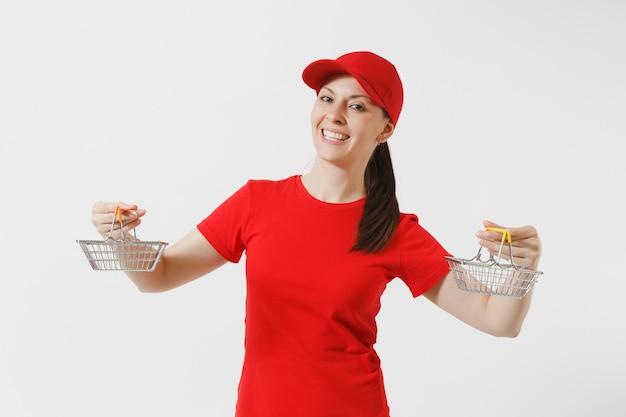 Kobieta dostawy w czerwonym mundurze na białym tle. kobieta kurier lub sprzedawca w czapce, t-shirt, dżinsy trzymając metalowy kosz na zakupy w supermarkecie. skopiuj miejsce na reklamę.