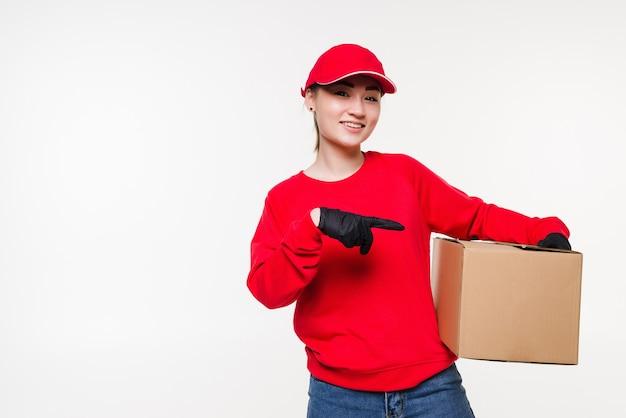 Kobieta dostawy w czerwonym mundurze na białym tle. kurier w rękawiczkach medycznych, czapce, czerwonej koszulce, jako dealer trzymający karton do dostawy. otrzymanie paczki.