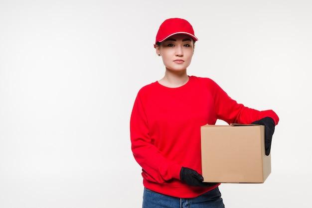 Kobieta dostawy w czerwonym mundurze na białym tle na białej ścianie. kurier w rękawiczkach medycznych, czapce, czerwonej koszulce, jako dealer trzymający karton do dostawy. otrzymanie paczki.