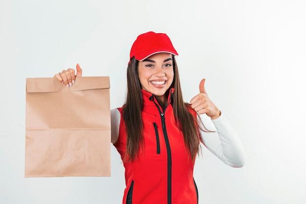 Kobieta dostawy w czerwonym mundurze trzyma pakiet papieru rzemieślniczego z jedzeniem