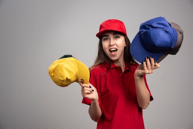 Kobieta dostawy w czerwonym mundurze, trzymając kolorowe czapki.