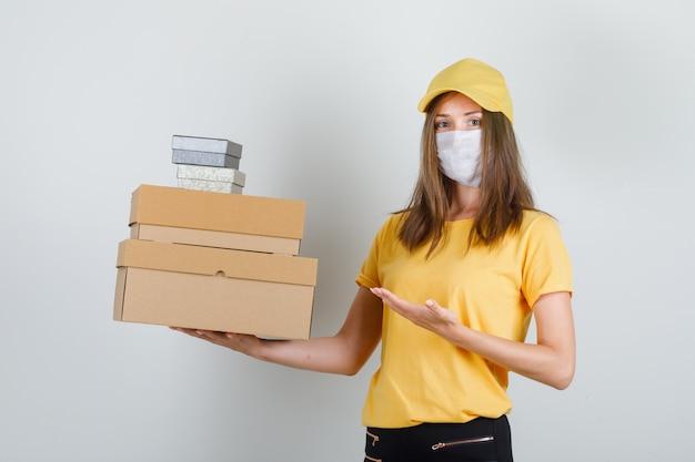 Kobieta dostawy w koszulce, spodniach, czapce, masce pokazującej pudełka i wyglądającej wesoło
