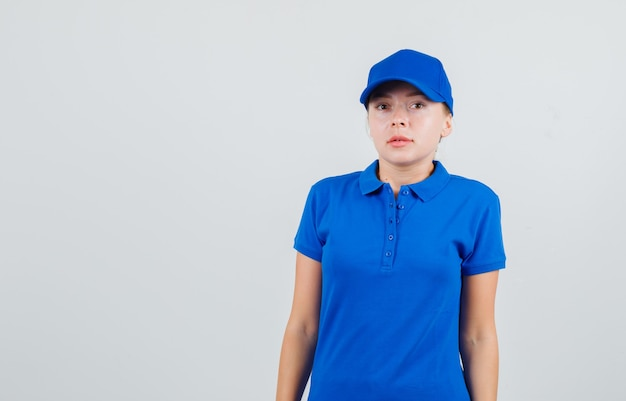 Kobieta dostawy w niebieskiej koszulce i czapce wygląda i patrzy zdziwiona