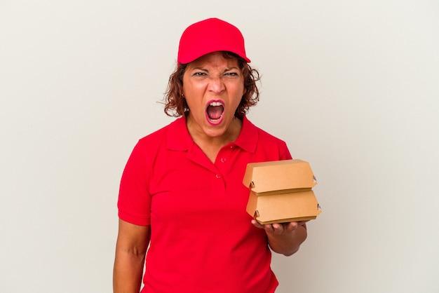 Kobieta dostawy w średnim wieku biorąc hamburgery na białym tle krzycząc bardzo zły i agresywny.