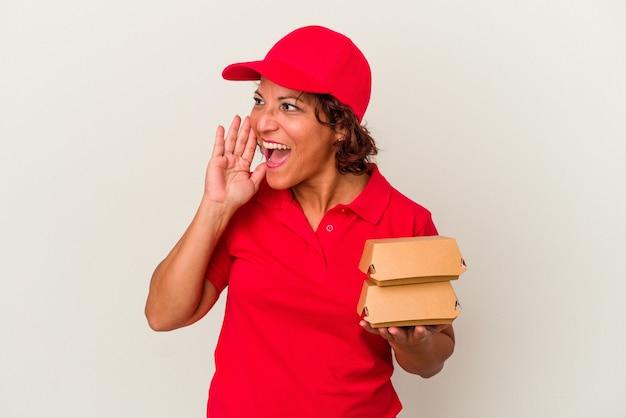 Kobieta dostawy w średnim wieku biorąc hamburgery na białym tle krzycząc i trzymając dłoń w pobliżu otwartych ust.