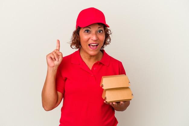 Kobieta dostawy w średnim wieku biorąc hamburgery na białym tle o jakiś świetny pomysł, pojęcie kreatywności.