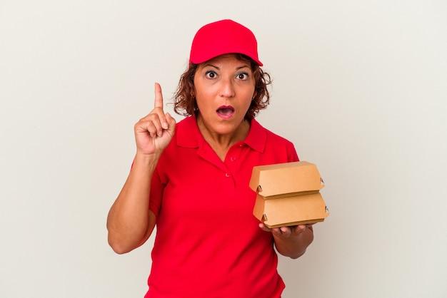 Kobieta dostawy w średnim wieku biorąc hamburgery na białym tle o pomysł, koncepcja inspiracji.