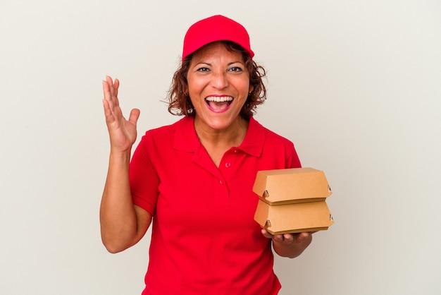 Kobieta dostawy w średnim wieku biorąc hamburgery na białym tle odbiera miłą niespodziankę, podekscytowana i podnosząc ręce.