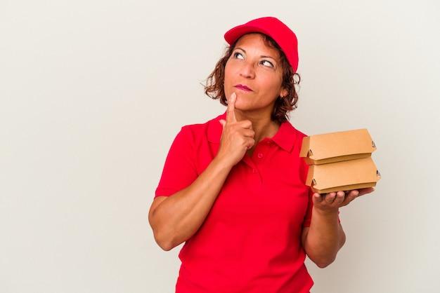 Kobieta dostawy w średnim wieku biorąc hamburgery na białym tle patrząc w bok z wyrazem wątpliwości i sceptyczny.