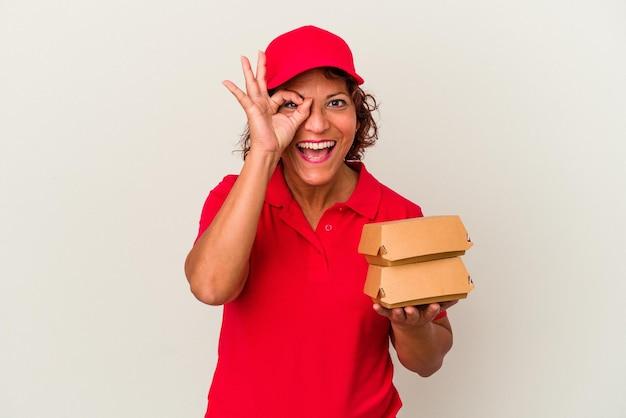 Kobieta dostawy w średnim wieku biorąc hamburgery na białym tle podekscytowany utrzymanie ok gest na oko.