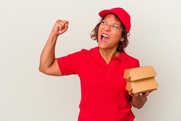 Kobieta dostawy w średnim wieku biorąc hamburgery na białym tle podnosząc pięść po zwycięstwie, koncepcja zwycięzca.