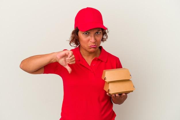 Kobieta dostawy w średnim wieku biorąc hamburgery na białym tle pokazując gest niechęci, kciuk w dół. koncepcja niezgody.