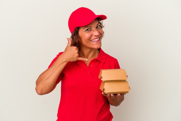 Kobieta dostawy w średnim wieku biorąc hamburgery na białym tle pokazując gest połączenia z telefonem komórkowym palcami.