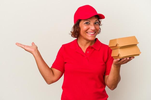 Kobieta dostawy w średnim wieku biorąc hamburgery na białym tle pokazując miejsce kopii na dłoni i trzymając drugą rękę na pasie.