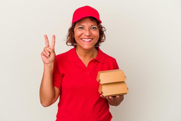 Kobieta dostawy w średnim wieku biorąc hamburgery na białym tle pokazując numer dwa palcami.