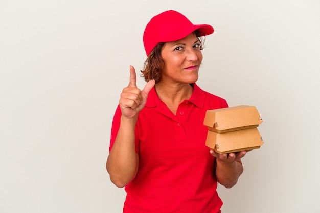 Kobieta dostawy w średnim wieku biorąc hamburgery na białym tle pokazując numer jeden z palcem.