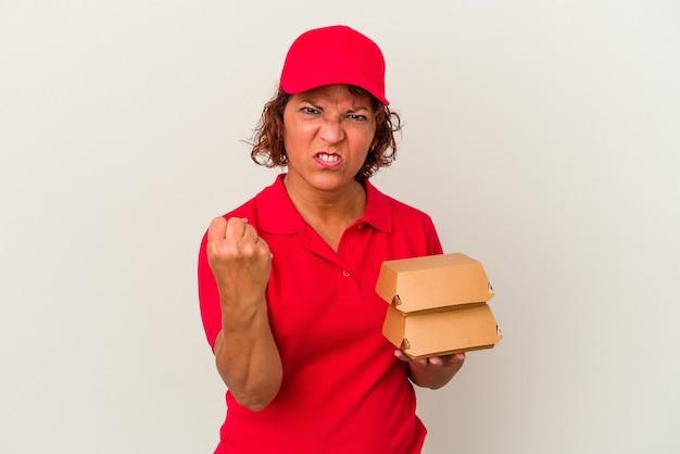 Kobieta dostawy w średnim wieku biorąc hamburgery na białym tle pokazując pięść do kamery, agresywny wyraz twarzy.