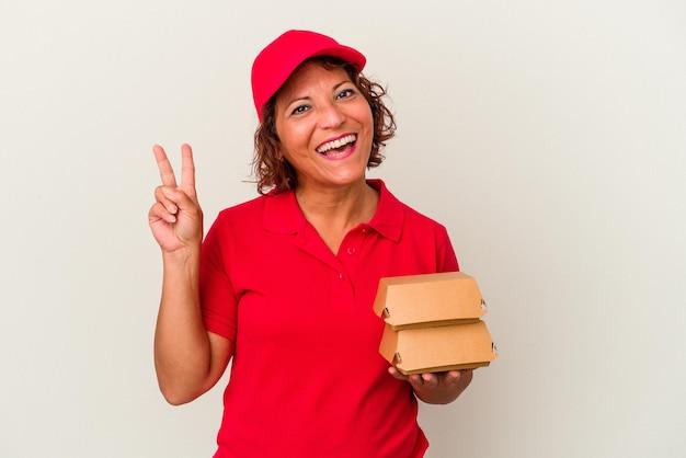 Kobieta dostawy w średnim wieku biorąc hamburgery na białym tle radosny i beztroski pokazując symbol pokoju palcami.