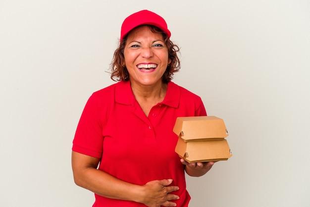 Kobieta dostawy w średnim wieku biorąc hamburgery na białym tle śmiejąc się i zabawę.