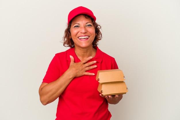 Kobieta dostawy w średnim wieku biorąc hamburgery na białym tle śmieje się głośno trzymając rękę na klatce piersiowej.