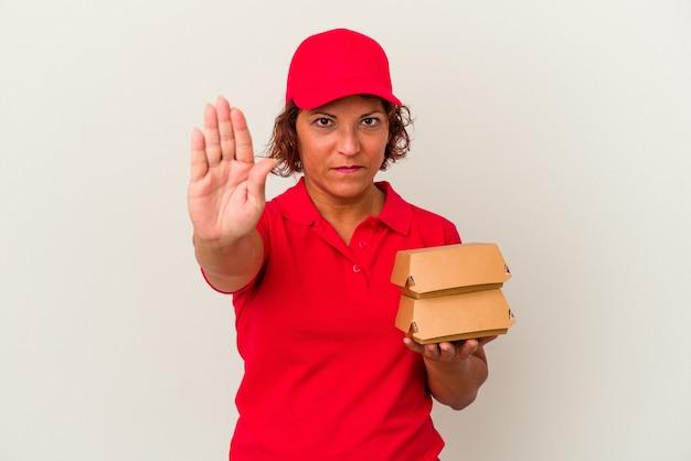 Kobieta dostawy w średnim wieku biorąc hamburgery na białym tle stojąc z wyciągniętą ręką pokazując znak stop, uniemożliwiając.