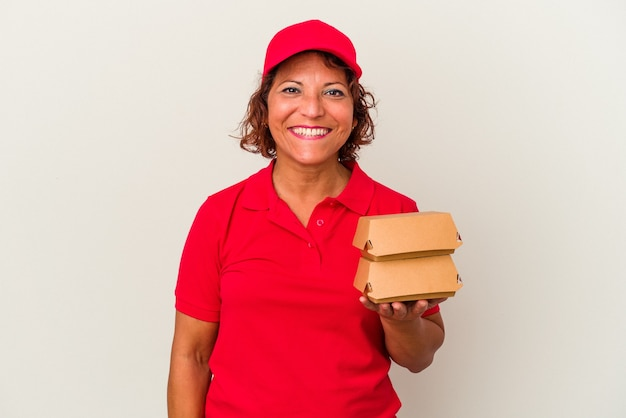 Kobieta dostawy w średnim wieku biorąc hamburgery na białym tle szczęśliwy, uśmiechnięty i wesoły.