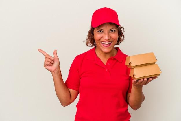 Kobieta dostawy w średnim wieku biorąc hamburgery na białym tle uśmiechając się i wskazując na bok, pokazując coś w pustej przestrzeni.