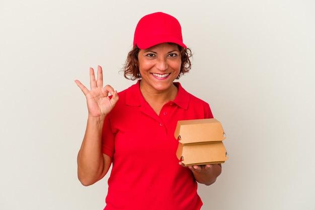 Kobieta dostawy w średnim wieku biorąc hamburgery na białym tle wesoły i pewny siebie, pokazując ok gest.