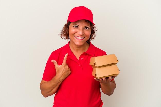 Kobieta dostawy w średnim wieku biorąc hamburgery na białym tle wskazując palcem na ciebie, jakby zapraszając się bliżej.