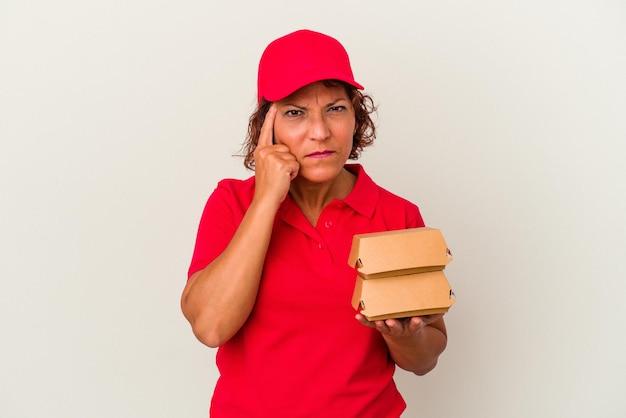Kobieta dostawy w średnim wieku biorąc hamburgery na białym tle wskazując świątynię palcem, myśląc, koncentruje się na zadaniu.