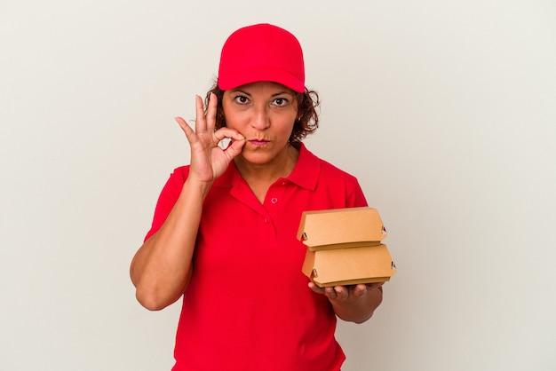 Kobieta dostawy w średnim wieku biorąc hamburgery na białym tle z palcami na ustach zachowując tajemnicę.