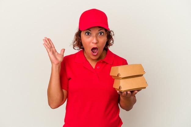 Kobieta dostawy w średnim wieku biorąc hamburgery na białym tle zaskoczony i zszokowany.