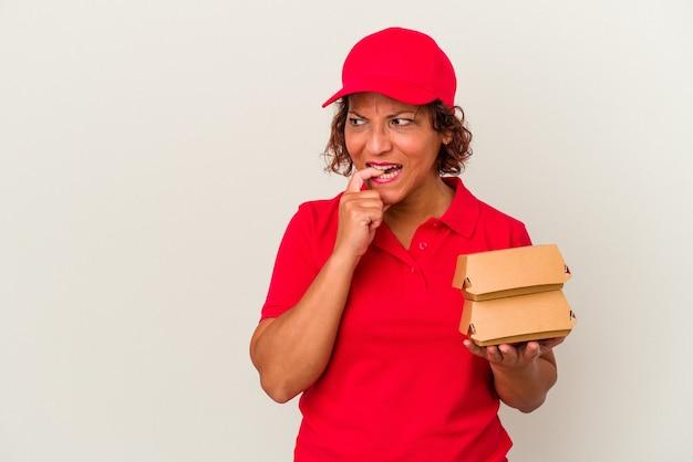 Kobieta dostawy w średnim wieku biorąc hamburgery na białym tle zrelaksowana myślenie o czymś patrząc na miejsce na kopię.