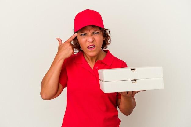 Kobieta dostawy w średnim wieku biorąc pizze na białym tle pokazując gest rozczarowania palcem wskazującym.