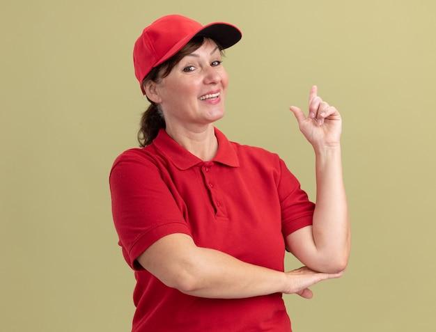 Kobieta dostawy w średnim wieku w czerwonym mundurze i czapce patrząc na przód uśmiechnięta pewnie pokazując palec wskazujący o nowym świetnym pomyśle stojącym nad zieloną ścianą
