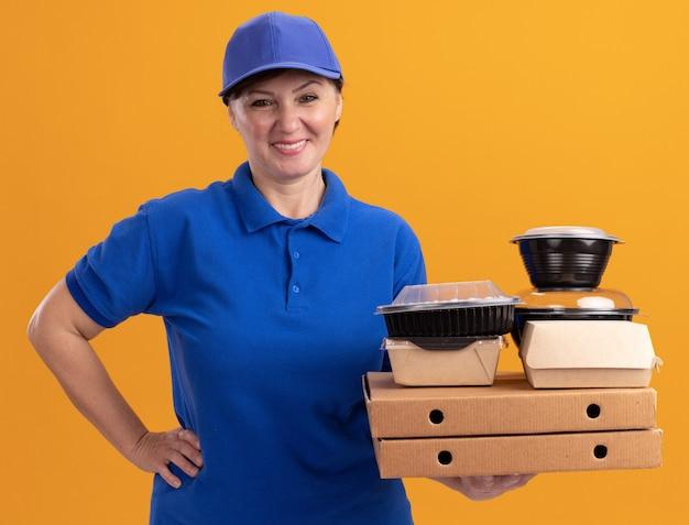 Kobieta dostawy w średnim wieku w niebieskim mundurze i czapce, trzymając pudełka po pizzy i opakowania żywności, patrząc na przód uśmiechnięta pewnie stojąca nad pomarańczową ścianą