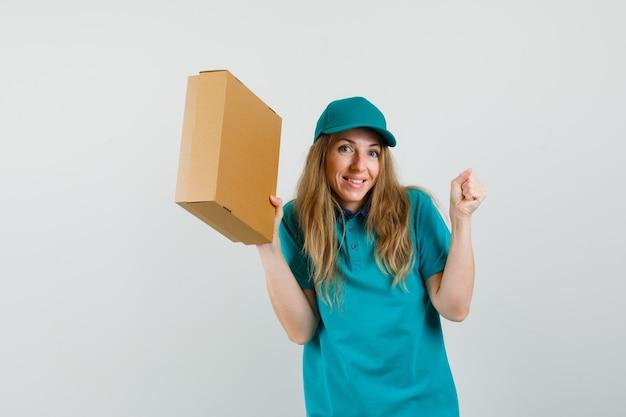 Kobieta dostawy w t-shirt, czapce trzymającej karton z gestem zwycięzcy i wyglądającej na szczęśliwą