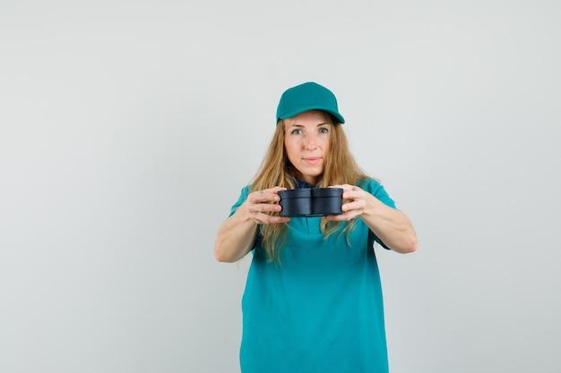 Kobieta dostawy w t-shirt, czapka prezentująca pudełko i patrząc wesoło