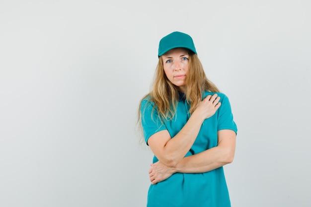Kobieta dostawy w t-shirt, czapka trzymająca rękę na piersi