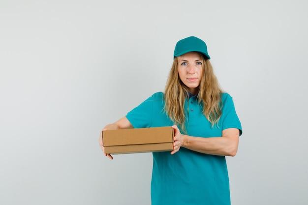 Kobieta dostawy w t-shirt, czapkę trzymając karton i uśmiechnięty
