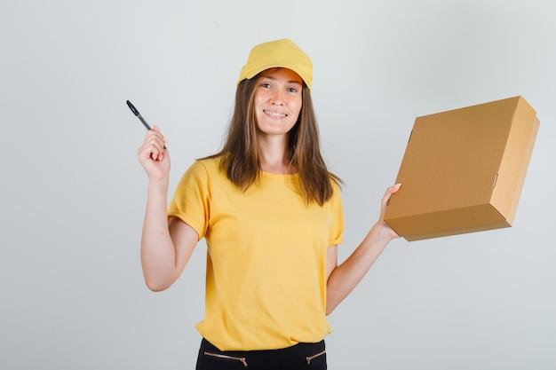 Kobieta dostawy w t-shirt, spodnie, czapkę trzymająca karton i długopis i wyglądająca wesoło