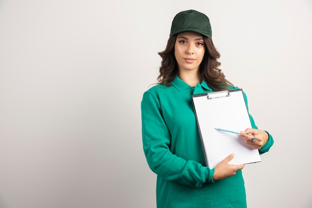 Kobieta dostawy w zielonym mundurze pokazując szczegóły zamówienia.