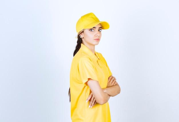 Kobieta dostawy w żółtym mundurze stojąc i patrząc na kamery.
