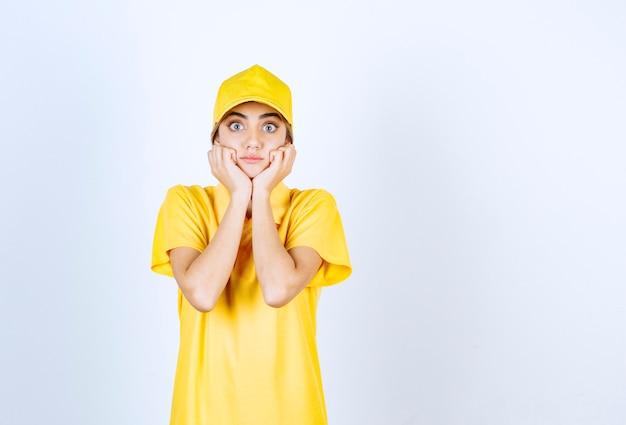 Kobieta dostawy w żółtym mundurze stojąc i pozowanie.
