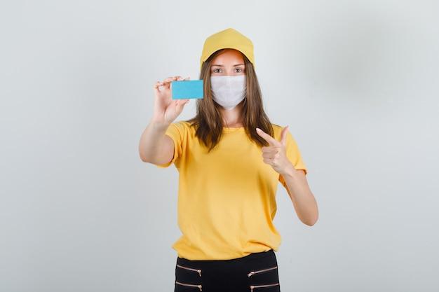 Kobieta dostawy wskazując palcem na niebieską kartę w koszulce, spodniach, czapce i masce i patrząc zadowolony