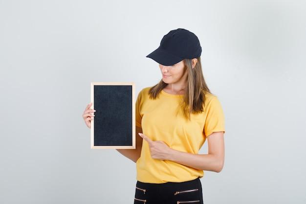 Kobieta dostawy wskazując palcem na tablicy w koszulce, spodniach, czapce i patrząc zadowolony