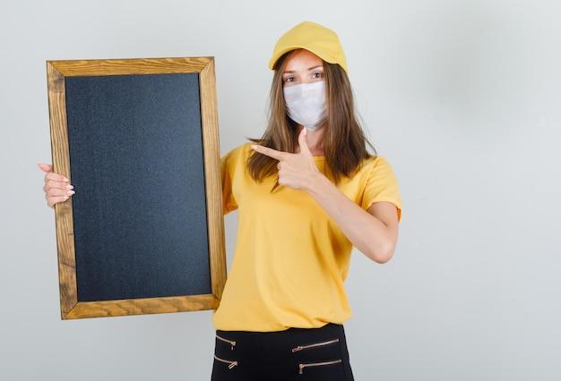 Kobieta dostawy wskazując palcem na tablicy w t-shirt, spodnie, czapkę i maskę
