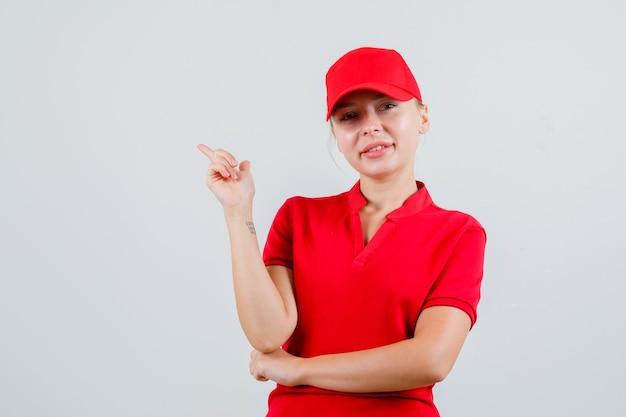 Kobieta dostawy wskazując w czerwoną koszulkę i czapkę i patrząc wesoło