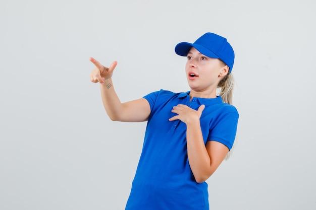 Kobieta dostawy wskazując w niebieską koszulkę i czapkę i patrząc ostrożnie
